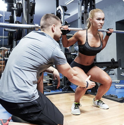 Trainer teaching a squat
