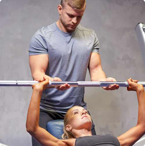 Trainer teaching a bench press